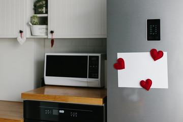 Handmade red felt heart shape magnets on refrigerator door.