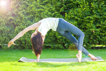pretty adult woman doing yoga at summer morning