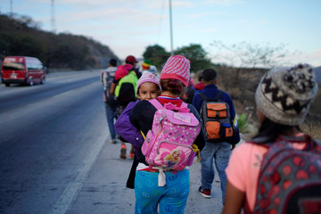 Five years old Soe Morales peers to the camera while being carried by her mother during their journey towards the United States, in Guastatoya, Guatemala