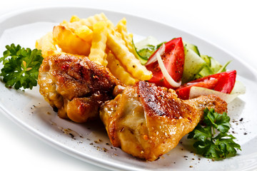 Drumsticks with french fries and vegetable on white background