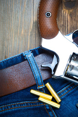 silvery revolver nagant with cartridges on old blue jeans