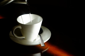Filling hot water from kettle to empty white glass with saucer and metal spoon in the dark corner with beautiful sunlight on wooden glossy table