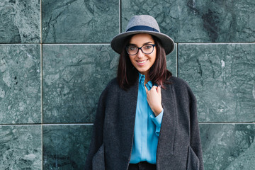 Joyful stylish young woman in grey hat, coat, black glasses smiling to camera on grey background on street. Luxury clothes, fashionable model, cheerful mood