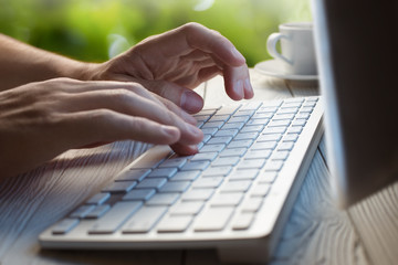 Close-up picture of male hands typing on desktop computer keyboard