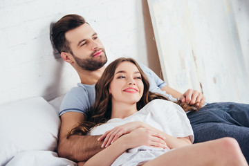 adult loving man gentle embracing woman in bed