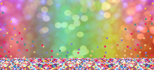 Colorful confetti in front of colorful background with bokeh for carnival