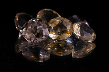 Group of big white and yellow transparent diamond shaped stones on a reflecting surface surrounded with a black studio background