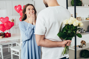 partial view of a young man holding bouquet of roses behind back while smiling girlfriend waiting for surprise