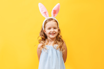 Portrait of a cute little child girl with bunny ears on a colore