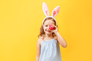 Cheerful little kid girl with bunny ears with an easter egg on a