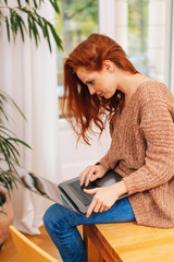 Red-haired woman with laptop sitting on table