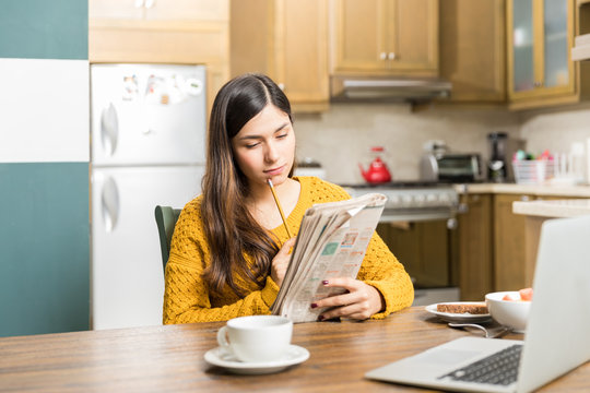 Woman Analyzing Newspaper Game Carefully