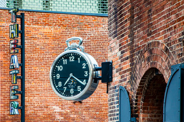 Stylish public analog clock hanging on brick wall showing time in Brooklyn, New York, USA during daytime