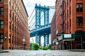 Zelfklevend Fotobehang Brooklyn Bridge Manhattan Bridge between Manhattan and Brooklyn over East River seen from a narrow alley enclosed by two brick buildings on a sunny day in Washington street in Dumbo, Brooklyn, NYC