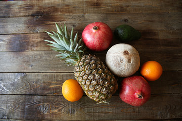 tropical fresh fruits: pineapple, oranges, pomegranate, avocado and coconut on a wooden rustic table with space for text top view
