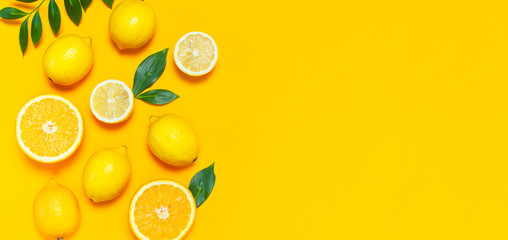 Ripe juicy lemons, orange and green leaves on bright yellow background. Lemon fruit, citrus minimal...