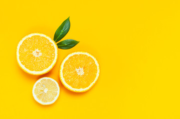 Wall Mural - Ripe juicy lemons, orange and green leaves on bright yellow background. Lemon fruit, citrus minimal concept, vitamin C. Creative summer minimalistic background. Flat lay, top view, copy space.