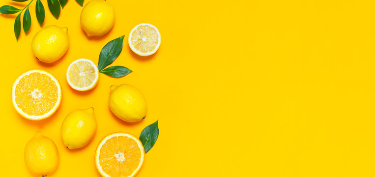 Ripe juicy lemons, orange and green leaves on bright yellow background. Lemon fruit, citrus minimal concept, vitamin C. Creative summer minimalistic background. Flat lay, top view, copy space.
