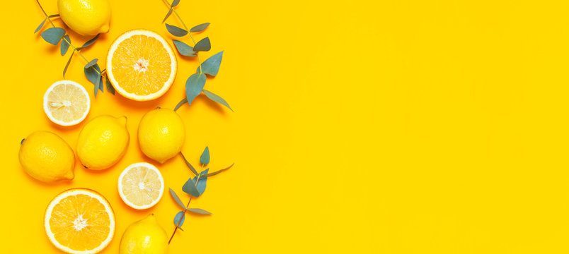 Ripe juicy lemons, orange and green eucalyptus twigs on bright yellow background. Lemon fruit, citrus minimal concept, vitamin C. Creative summer minimalistic background. Flat lay, top view copy space