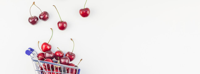 Ripe cherries in a shopping cart isolated
