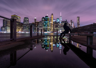 View on Financial district from the pier with man on the bench and water reflection at night with long exposure