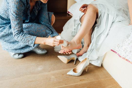 Wedding preparations. Bridesmaid applies powder to the bride's leg to wear bridal shoes comfortably