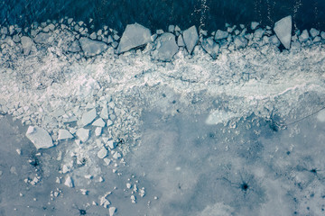 Glacier Lagoon with icebergs from above. Aerial View. Cracked Ice from drone view. Background texture concept. Wall mural