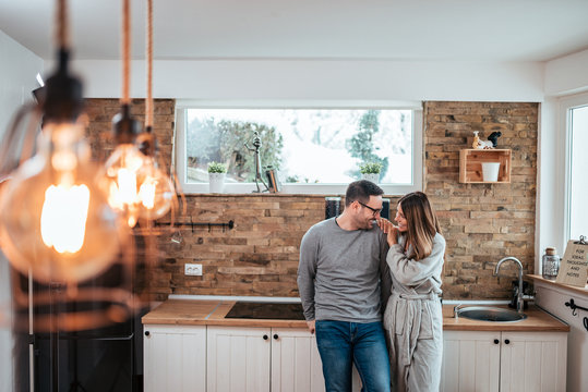 Portrait of a couple in love in the kitchen at home on winter morning.
