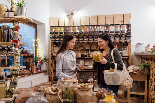 Young woman buying fresh spices and herbs at package free grocery store.