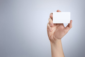 Hand showing white card on gray background