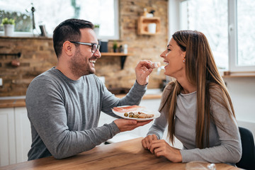 Handsome man feeding his girlfriend at the kitchen table at home.