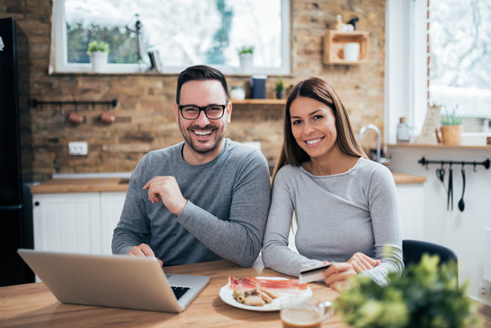 Portrait of a cheerful young couple at the kitchen table with laptop and breakfast, looking at camera.