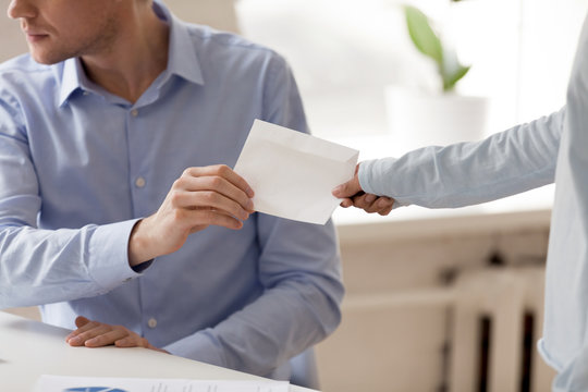 Close up businessman taking envelope with bribe from woman, client giving, offering money to dishonest man, making secret illegal deal, partners planning fraud, hands view, corruption concept