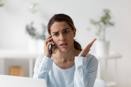 Upset unpleasantly surprised woman making phone call, disputing, complaining, having bad conversation with friend or client, businesswoman receiving bad news, using smartphone, solving problem