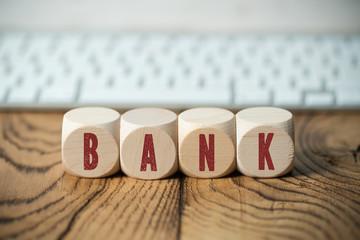 Würfel mit Aufschrift BANK vor Tastatur