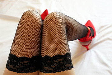 Sexy female legs in black fishnet stockings and red velvet shoes on high heels. Seductive girl lying on the bed, concept of sex dating, female fashion