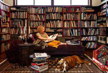 Smiling woman with dog reading book on sofa at home