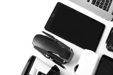 modern gadgets on a white background, a tablet with a dark screen next to the drone and laptop