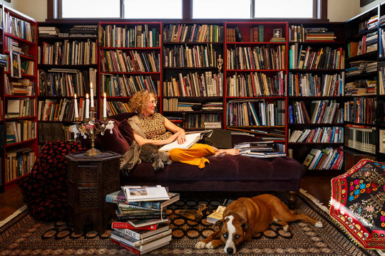 Woman with dog sitting on sofa at home