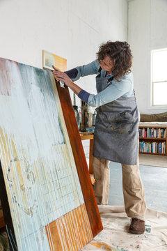 Creative woman artist working painting in her studio