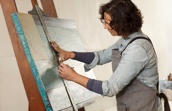 Creative woman artist working on a painting in her studio