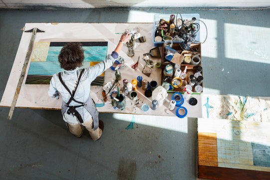 Creative woman artist working on a painting using art supplies in her studio
