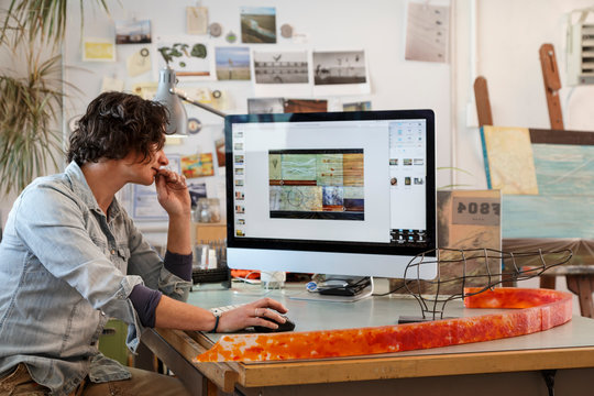 Creative woman artist working using a desktop computer monitor workstation in her studio office