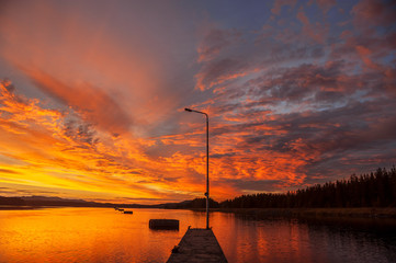 Sunset on the river. Pier with light pole in the foreground.