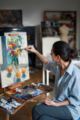 A young woman artist paints a picture in oil on the easel. The woman loose comfortable casual clothing. Vertical photo.