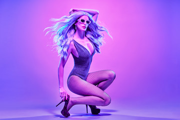 Disco Party Doll girl with Purple hairstyle dance. High Fashion. Young Gorgeous model woman in Colorful neon Light. Night Clubbing. Music vibes. Pop Art Style