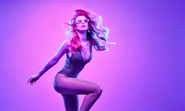 High Fashion. Gorgeous Disco Party girl with glowing hair dance. Young beautiful model woman in Colorful neon Light. Night Clubbing. Stylish fashionable banner