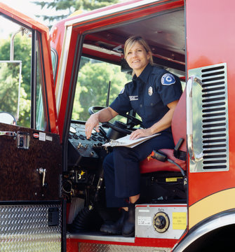 Smiling female woman firefighter sitting in driver's seat of fire engine truck. Confident, successful blue collar worker.