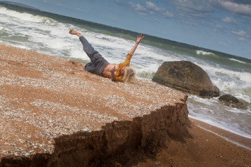 Performer girl dancing on a splash background in the sea surf.