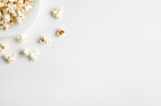 Background with a plate of popcorn. White background with popcorn. Place for inscription